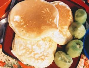 Trois pancakes servis avec des kiwis